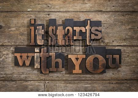 it starts with you, phrase written with vintage letterpress printing blocks on rustic wooden background