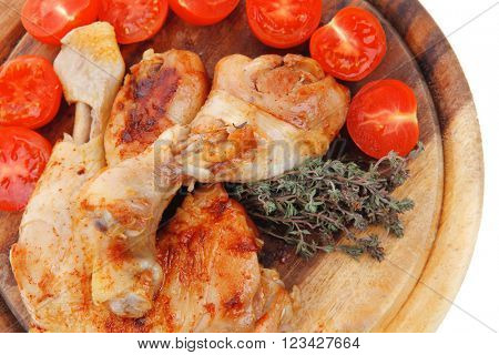 grilled chicken drumstick with tomatoes and thyme on wooden plate isolated over white background