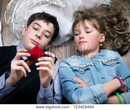 Teens - Young man and woman lying on the floor. Casket for jewelry. Concept - an engagement, marriage proposal, a declaration of love. First love