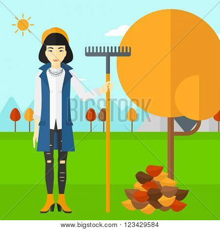Woman with rake standing near tree and heap of autumn leaves.