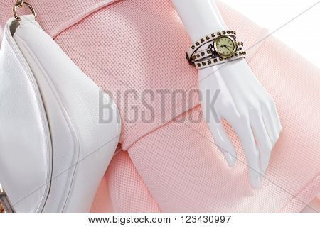 Purse and watch on mannequin. Female mannequin with stylish watch. White leather purse and watch. Classic watch and leather handbag.