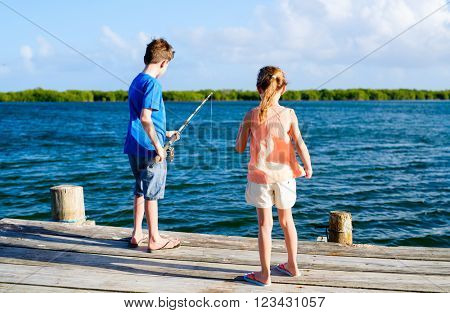 Kids brother and sister fishing together from wooden jetty