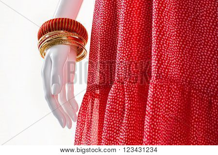 Golden bracelets on mannequin's hand. Female mannequin with stylish bracelets. Set of bright female bracelets. Simple merchandise at nice discount.