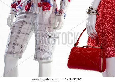 Handbag and shorts on mannequins. Mannequins in new light clothes. Leather purse and men's shorts. Summer clothes with stylish accessories.
