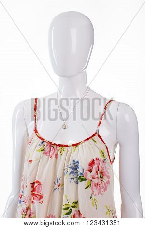 Sarafan with pendant on mannequin. Female mannequin in light dress. Floral clothing and small accessory. Casual garment with expensive jewelry.