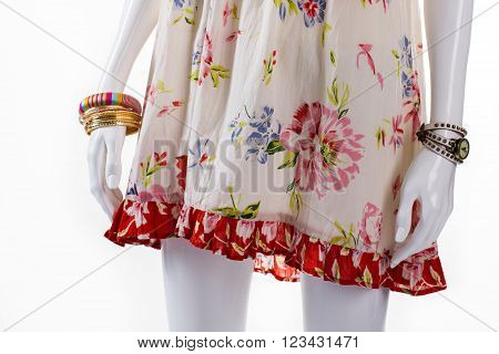Bracelet and watch on mannequin. Female mannequin with small accessories. Floral sarafan and bracelets set. New arrivals of clothing.