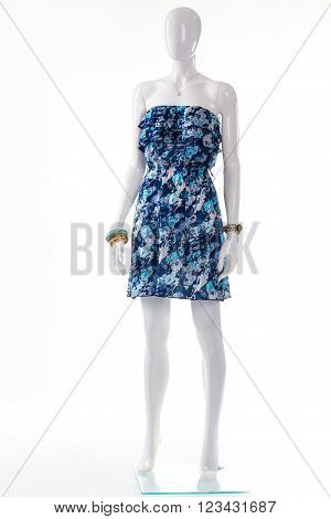 Blue dress on white mannequin. Female mannequin in vintage dress. Strapless retro dress and accessories. Young lady's classy summer outfit.