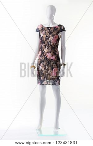 Floral evening dress on mannequin. Female mannequin in evening garment. Dark dress with beige lining. Floral dress with bateau neckline.