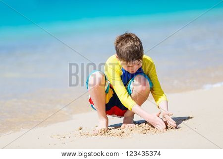 Handsome pre-teen age boy playing with sand at tropical beach on summer vacation