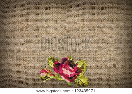 horizontal background of coarse burlap embroidered cross-stitch rose closeup