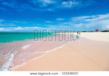 Two kids happily running at unique Pink sand beach on tropical Barbuda island in Caribbean