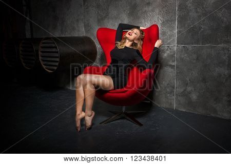 Beautiful blonde girl in a black slinky dress sitting in the red chair. girl in an easy relaxed position sits in the chair.  Woman laughing in a chair.