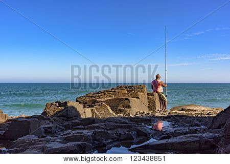 Fisherman sitting on Guarita stone watching the sea in Torres city Rio Grande do Sul