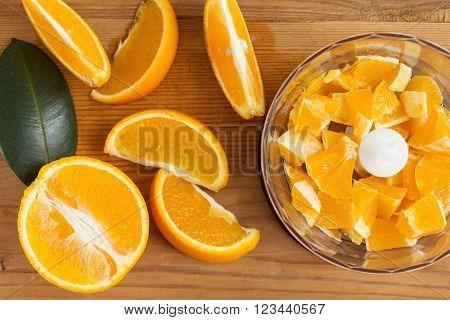 Blender with juicy oranges on the kitchen table. Oranges in a blender.