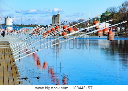 Ahus Sweden - March 20 2016: The mooring buoys are raised during winter to protect them from the ice. Here they are in early spring ready to be lowered and used as a marina in the canal.