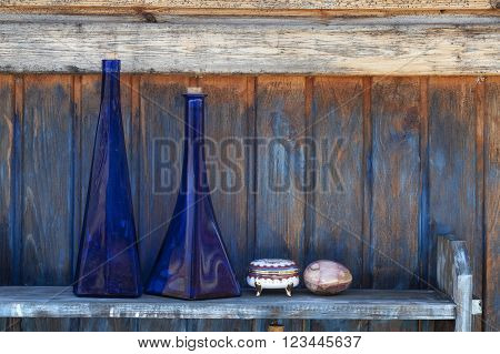Blue glass decorative bottles placed on a shelf against the painted wooden wall