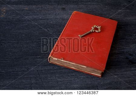 Still life with old book and key on old wooden table