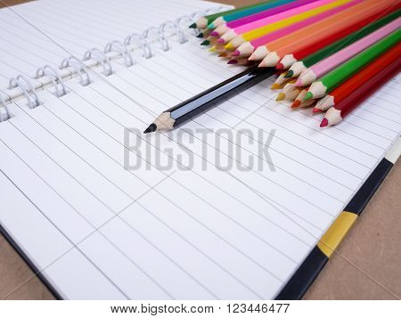 Black pencil standing out from a stack of color pencil on white notebook leadership business concept
