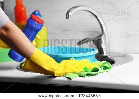 Female hands with rag and detergent bottle cleaning a sink in the kitchen
