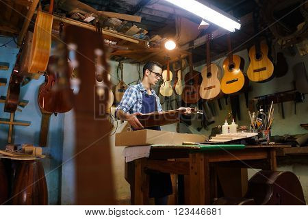 Lute maker shop and acoustic music instruments: a young adult artisan fixes an old classic guitar then stores it in a cardboard case for his client. Wide shot