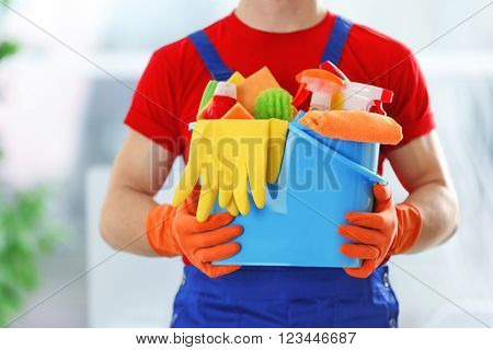 Young janitor holding cleaning products and tools on bucket, close up