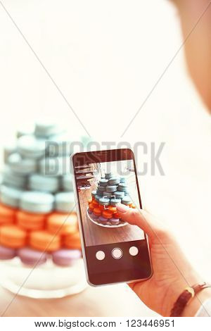 Woman making photo of varicolored tasty macaroons with mobile phone