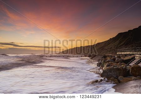 Looking along the coast at sunrise on Mundesley beach.