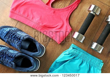 Athlete's set with female clothing, dumbbells on wooden background