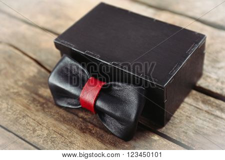 Black and red leather bow tie and gift box  on wooden table, close up