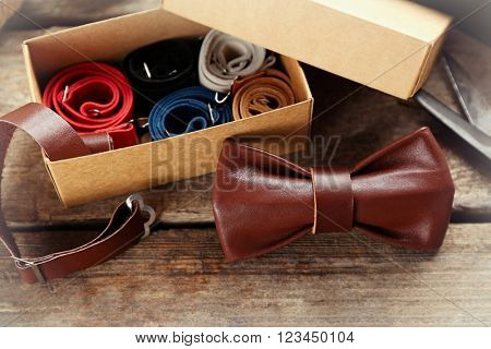 Brown leather bow tie and full cardboard gift box of ties on wooden table, close up