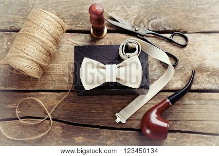 White leather bow tie and black gift box with crafts and tobacco pipe on wooden table, top view