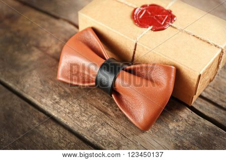 Light-brown and black leather bow tie and cardboard gift box with red seal on wooden table, close up