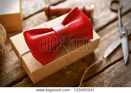 Red leather bow tie and cardboard gift box with red seal on wooden table, close up
