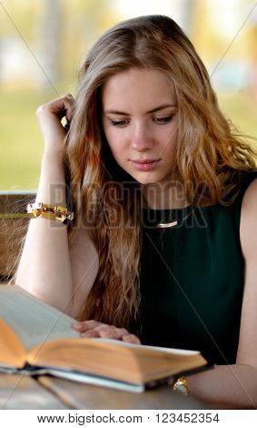 Very beautiful, snorting, stunning, attractive, adorable, perfect, awesome, gorgeous, excellent, pretty, nice, good, lovely, blonde, long-haired girl sitting with book. Nice girl read book. Beautiful girl with book.