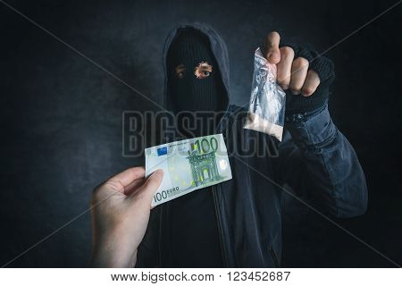 Drug dealer offering narcotic substance to addict on the street unrecognizable hooded criminal selling drugs in dark alley for euro banknotes