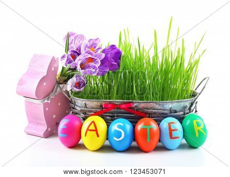 Multicoloured Easter eggs in a wicker bowl and decor isolated on white