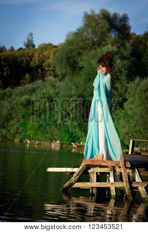 Chic, classy, beautiful, attractive, adorable, stunning, snorting, gorgeous, pretty, nice, awesome, excellent girl, model near the blue lake, green trees in blue dress. Fashionable diva, goddess in blue, long dress.