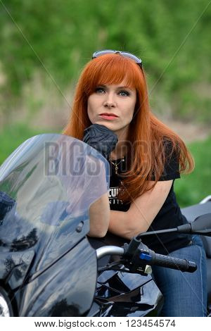 Serious, red-haired, sports woman with bike, beautiful, angry, powerful, red-haired, young girl with black motorbike, girl with motorcycle, sitting on motorbike with sunglasses, leather gloves, serious face, bike
