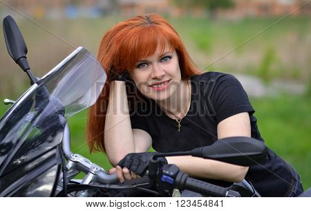 Interesting, cheerful, nice, good, friendly, lovely, adorable, red-haired professional biker girl with black, fast motorcycle, cute smile. Girl with motorbike, fast rider.