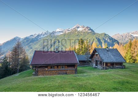 wooden chalets on mountain meadow at austrian alps