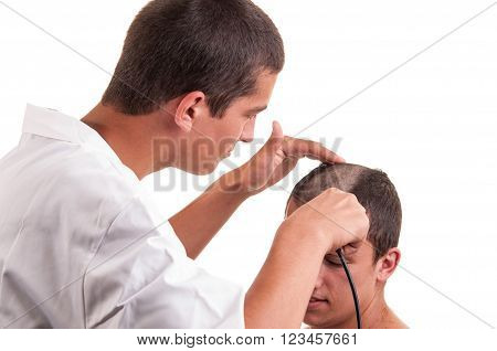 Barber cutting hair of a young man with clipper on white