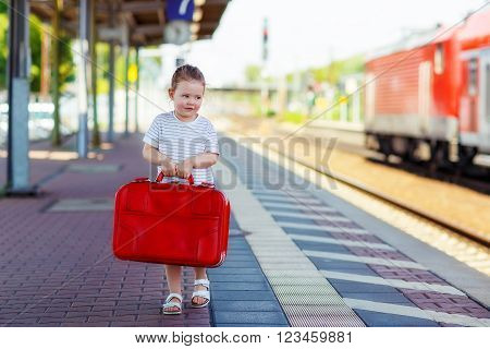 Toddler girl of 3 years walking with big red suitcase on a railway station. Kid waiting for train and happy about a journey. People, travel, lifestyle concept