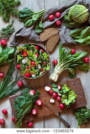 Spring vegetable diet salad with radish, cucmber, savoy cabbage, parsley, green onion, ramson leek and bread. Healthy vegetarian food.