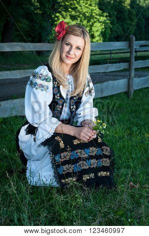 Beautiful Singer With Flowers Posing In Traditional Costume, Romanian Folklore