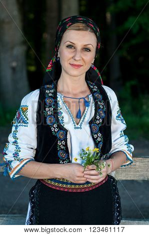 Beautiful Singer With Flowers In Her Hands Posing At Countryside, Romanian Folklore