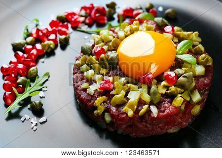Beef tartare served in a round black plate, close up