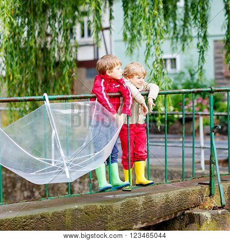 Two little brothers with big umbrella outdoors on rainy day. Kids boys having fun and wearing colorful waterproof clothes and rain boots.
