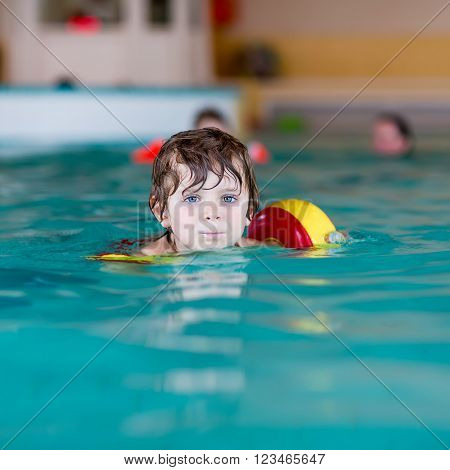 Funny little preschool boy with swimmies learning to swim in an indoor pool. Active and fit leisure for children.