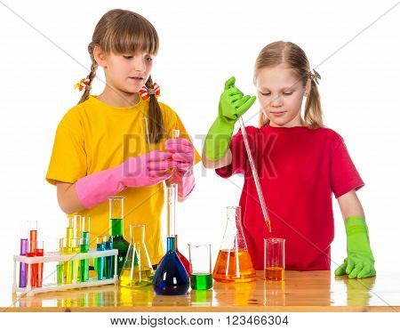 Two girl making a chemical experiment, standing on the table with scientific equipment, isolated on white