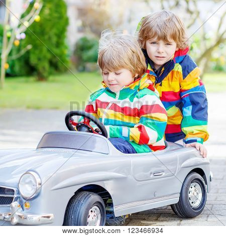Two happy sibling boys having fun with big old vintage toy car in spring or autumn garden, outdoors. Active leisure with kids outdoors  on warm spring or autumn day.